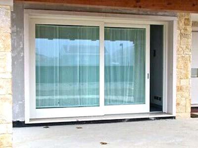 Serramenti in PVC scorrevoli bianchi installati in una portafinestra a Asti