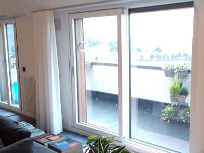 Serramenti in PVC scorrevoli bianchi installati in una portafinestra a Cremona