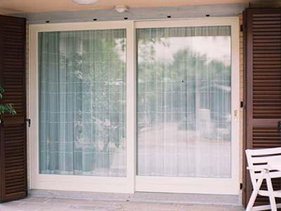 Serramenti in PVC scorrevoli bianchi installati in una portafinestra a Lecco