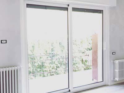 Serramenti in PVC scorrevoli bianchi installati in una portafinestra a Lodi