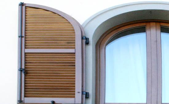 Persiana di legno realizzata su misura e montata su una portafinestra ad arco a tutto sesto